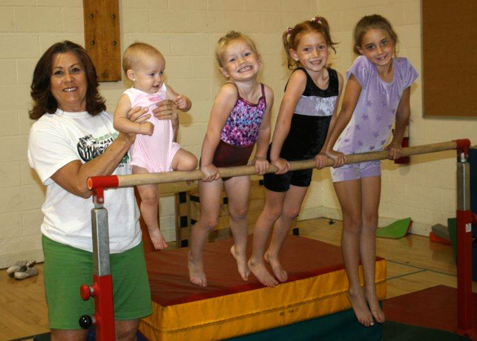 With huge smiles, Wawasee Gymnastics Club director Nika Prather works with campers (from left) Kaleigh Corn, Ashlyn Corn, Charlotte Crighton and Lily Crighton at the June 2013 camps.