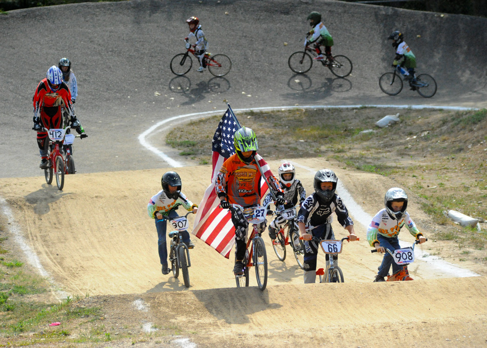 Caden Bowers of Warsaw carries the American flag through the Hire Park track during the National Anthem before racing Saturday morning.