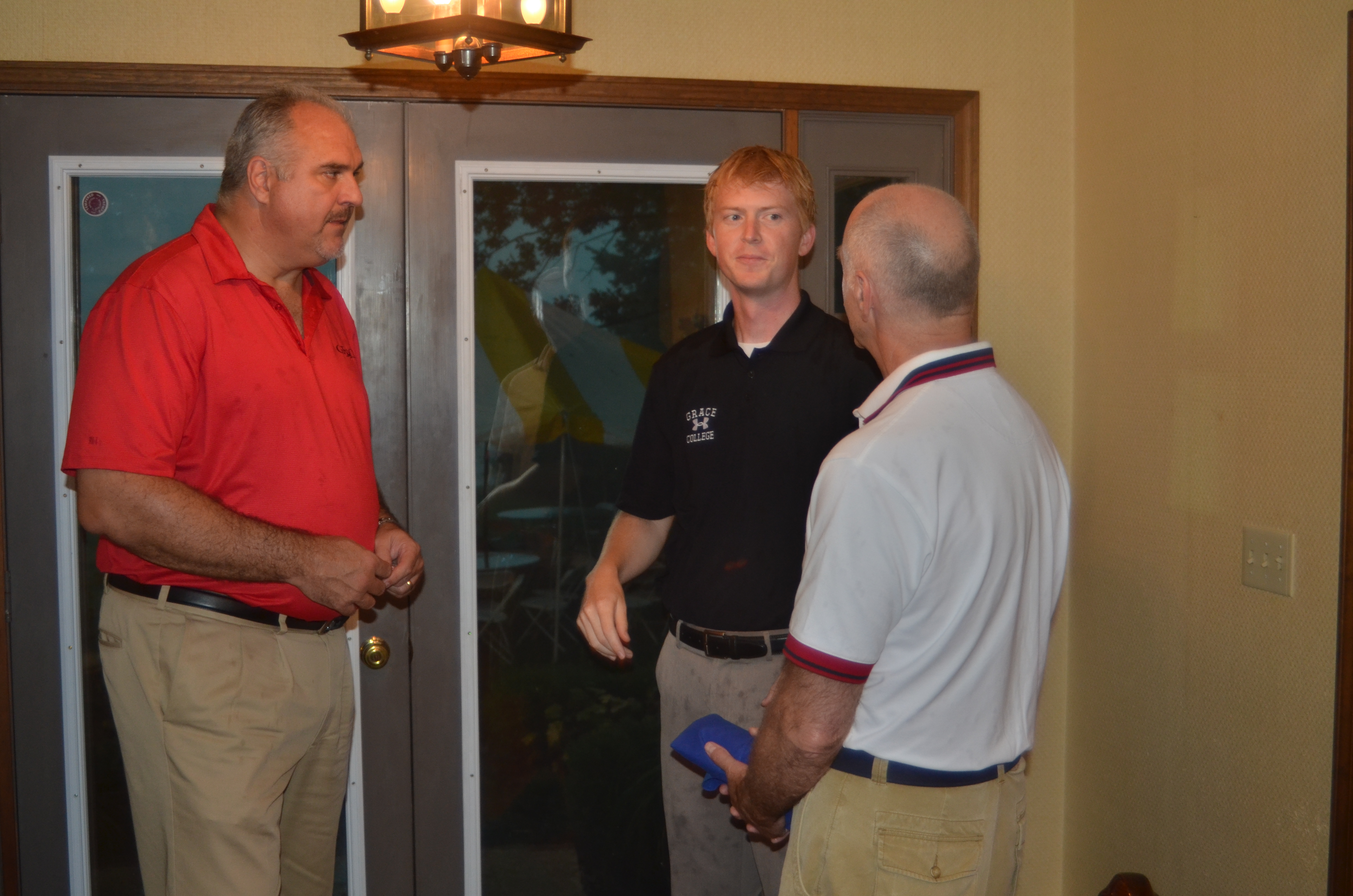 Dr. John R. Boel, vice president of advancement and chief advancement officer, left, and Dr. Nate Bosch, assistant professor of environmental biology and director of Kosciusko Lake and Stream water quality project, discuss projects and programs with Al Tehan, at a reception Saturday evening. An early evening storm halted the reception and tour of the Doug Anderson property and moved the event indoors. (Photo by Deb Patterson)