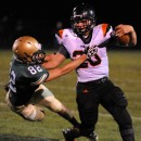 Warsaw running back Tristan McClone looks to shed the tackle of Wawasee's Brett Ward.