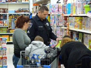 Warsaw Cpl. Jamie de la Fuente helps a local family shop during the annual Christmas with a Cop program. (Photo provided)