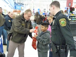 Kosciusko County FOP President Chris McKeand lends a hand to a child during the annual Christmas with a Cop program. (Photo provided)