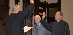 Outgoing circuit court judge Rex Reed, left, swears in newly elected circuit court judge Michael W. Reed while Reed's father, Max Reed, looks on. (Photo by Stacey Page)