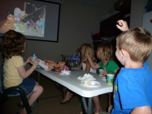 Children enjoy watching a slide-show of their stuffed animals' nighttime adventures during last summer's Stuffed Animal Sleepover at the North Webster Public Library.  Pictured from left are Mia Thornsbrough, Amanda Allen, Leona Sandoz and Griffin Sandoz.