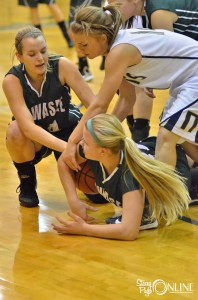 Wawasee guards Erin Wiktorowski (34) and Kylee Rostochak wrestle for a loose ball with Norwell's Liara Isnogle.