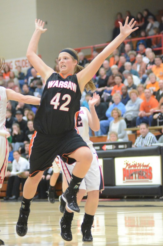 Nikki Grose of Warsaw goes flying after being hit on a drive to the basket Saturday night at NorthWood. The Panthers topped the Tigers 34-30 in NLC play.