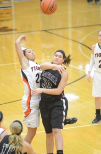 Warsaw senior standout Jennifer Walker-Crawford goes for the opening tip versus Mackenzie Kreutz of Lowell in the title game of the Lady Tiger Classic Dec. 27. The undefeated Tigers (11-0) are No. 10 in this week's Class 4-A poll.