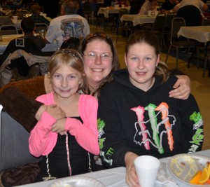 Mary Kester with her daughters, Rose Kester, in pink, and Tristen Barr. The family try to attend a few meals offered by Fellowship Missions throughout the year where they say they enjoy the fellowship and good food.