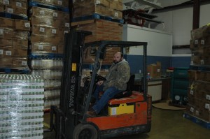 Bill Doege, warehouse worker for The Papers Inc. in Milford, is shown with some of the food stored in a warehouse of The Papers. Food is taken from the warehouse to a barn east of Milford where it is distributed monthly to various pantries in northern Indiana. (Photo by Tim Ashley)