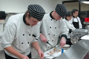 The culinary arts program at Wawasee High School gives students hands-on experience in food preparation and presentation using a professional-grade kitchen and equipment. Preparing a pork loin are Josh Secor and Cody Retcher. In the back are students Elaine Williams and Sara Christner.