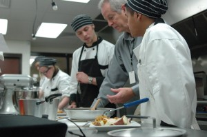 "Culinary arts teacher, Dan Bauer, explains a technique to Legend Laramore and Brandon Roche. In the back are students Maranda Loetz and Jose Rodriguez. ""I've had some of the most top notch kids in this class,"" said Bauer. ""There have been a few who struggle in their core classes, but excel at my class. Instead of reading books, they are experiencing hands-on learning."""