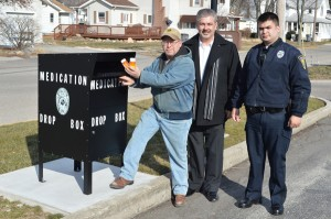 Paul Newcomer, left, president-elect ofWawasee Kiwanis, shows how easy it is to drop off expired or unwanted prescription medication at the new medication drop box on the northside of the Syracuse Town Hall. Wawasee Kiwanis donated funds toward the purchase and installation of the box. Shown to the right are Syracuse Police Chief TonyCiriello and officer Michael Bumbaugh. (Photo by Deb Patterson)