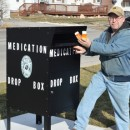 Paul Newcomer, left, president-elect of Wawasee Kiwanis, shows how easy it is to drop off expired or unwanted prescription medication at the new medication drop box on the northside of the Syracuse Town Hall. Wawasee Kiwanis donated funds toward the purchase and installation of the box. Shown to the right are Syracuse Police Chief Tony Ciriello and officer Michael Bumbaugh. (Photo by Deb Patterson)