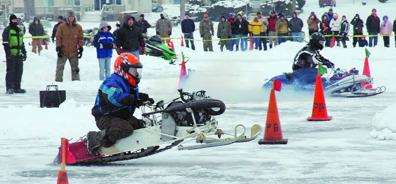 Two snowmobile racers take off during the 2011 Wawasee Kiwanis snowmobile drag races. This year's snowmobile drags, scheduled for Saturday, Jan. 26, are dependent on ice conditions. Alternative dates have been set, including Feb. 2. (File photo)