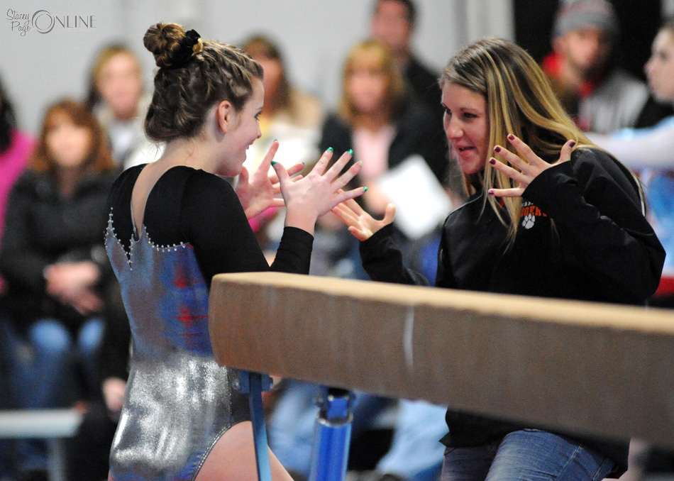 Warsaw head coach Andi Calhoun celebrates with gymnast Shannon Winslow after the sophomores beam performance at the Blazer Invite Thursday night. (Photos by Mike Deak)