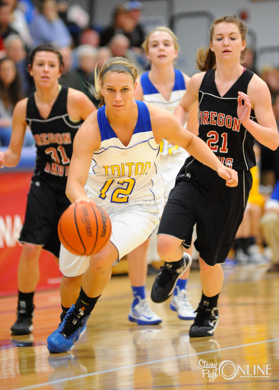 Triton's Breanna Lemler dribbles through Oregon-Davis defenders Jessica Avarone and Ashley Campbell at the girls basketball Bi-County Tournament championship Saturday night at LaVille High School. (Photos by Mike Deak)