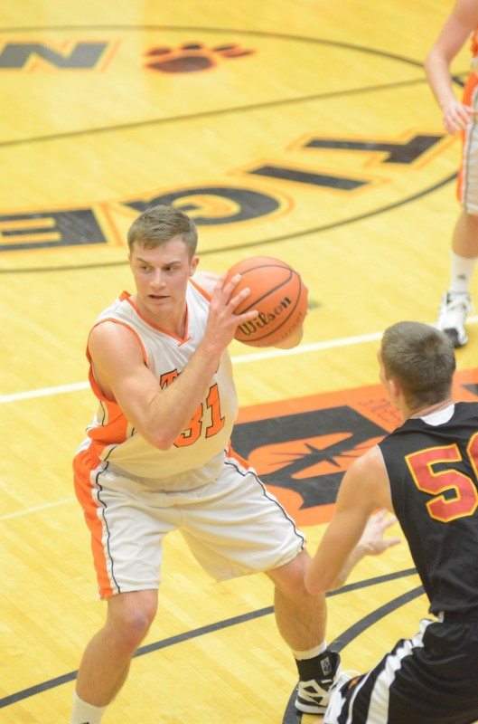Warsaw's Taylor Cone is defended by Evan Andersen of Memorial Friday night. Cone played a strong game with 13 points and eight rebounds in a 48-47 NLC loss.