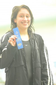 Warsaw junior Cynthia Juarez shows off her blue ribbon Saturday after earning a sectional title in the 500 freestyle.
