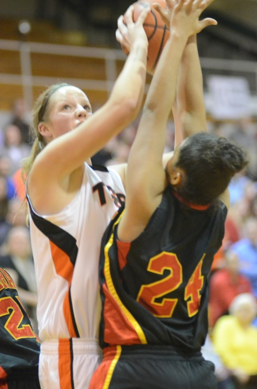 Warsaw's Nikki Grose goes up strong over Alyssa Wagner during sectional play Tuesday night at Concord. The No. 8 Tigers beat Elkhart Memorial 49-37.