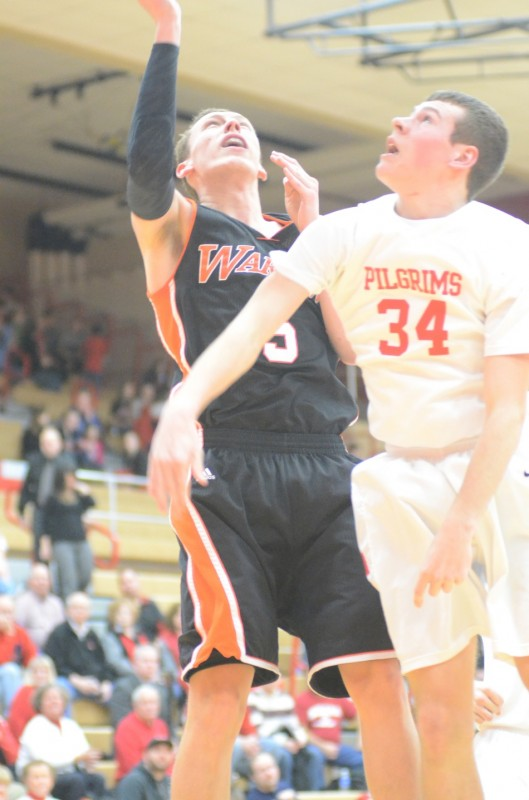 Senior John Swanson powers in two of his team-high 16 points for Warsaw over Trenton Briles of Plymouth.