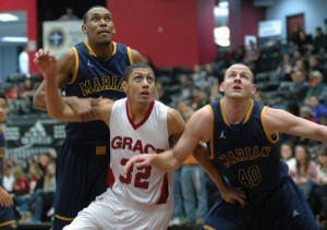 Freshman Brandon Vanderhegghen of Grace College, a Mishawaka native, battles for a rebound with a pair of Marian players at Grace Wednesday night (Photo provided by Grace College Sports Information Department)