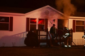 Firefighters enter the burning mobile home at Lot 128 in Green Acres Mobile Home Park. (Photo by Stacey Page)