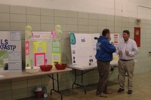 Judges Dino Coverstone, left, and Mike Smith discuss the science projects submitted to this year's Syracuse Elementary School Science Fair. Thirty projects were submitted by 40 students, and four were selected to represent the school at the regional science fair held at IPFW in March. (Photo by Rebekah Whirledge)
