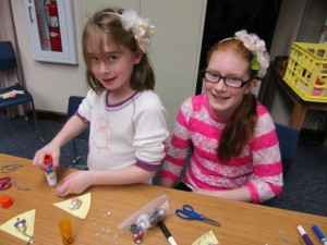 Some 60 kids came to Make It, Take It crafts on Feb. 11. Craft times are a good time to browse the latest arrivals while giving children a fun time at the library. Shown working on their Valentine gifts are sisters Adrianne and Allison Clark. (Photo provided)