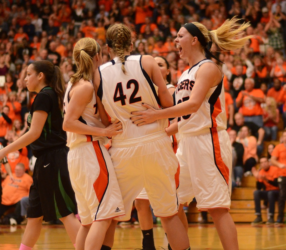 Warsaw senior Lindsay Baker (right) celebrates with teammates during the semi state Saturday night. Host Warsaw lost 47-44 to Fort Wayne South Side (Photos by James Harris)
