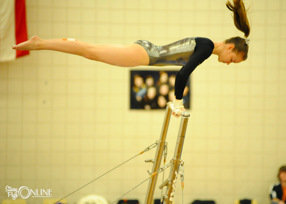 Warsaw's Jo Richard goes horizontal on the uneven bars Wednesday night in the meet against Elkhart Central. (Photos by Mike Deak)