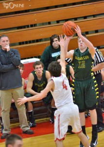 Wawasee's Jeffrey Moore shoots over Goshen's Austin Henke ahead of the watchful eye of Warrior head coach Phil Mishler Thursday night. (Photos by Nick Goralczyk)