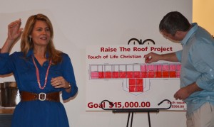 Lisa Whelchel speaks to a small crowd during a fundraising dinner Saturday night in Warsaw while Ryan Helser colors in a chart to show how much money was raised. (Photo by Stacey Page)