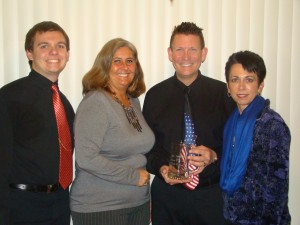 Because he had been called out of state on family business, Jay Johnson was present North Webster Person of the Year by Sue Ward, chamber president, before he left. His family Joined him for the honor. From the left are Ryan Johnson, son; Ward; Johnson; and wife, Sabrina Johnson. (Photo provided)