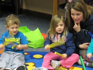 Counting time with the rhythm sticks are Liam Rumfelt and Leah Hurst. Mom, Sarah Hurst , enjoys the fun during Story Time at the Syracuse Library. (photo provided)