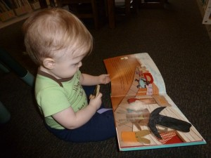 You're never too young to enjoy a good book as one-year-old Taryn Trafan discovers during a recent trip to the Library.  (photo provided)