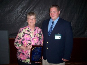 Crystal Weida, instructional assistant for the alternative education program at the Burket Educational Center, is retiring after nine years of dedicated service. Mrs. Weida was honored with a plaque during today's Graduate Honors Reception held in the Burket Historical Gymnasium. Pictured is Micah Lukens, instructor for the alternative education program, presenting a plaque to Mrs. Weida. (Photo provided)