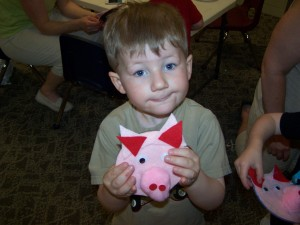 Kolbe Vint, Milford shows his piggy he made out of a cd.  He made it at story time at the Milford Public Library.  The theme for the day was Down on the Farm. (photo provided)