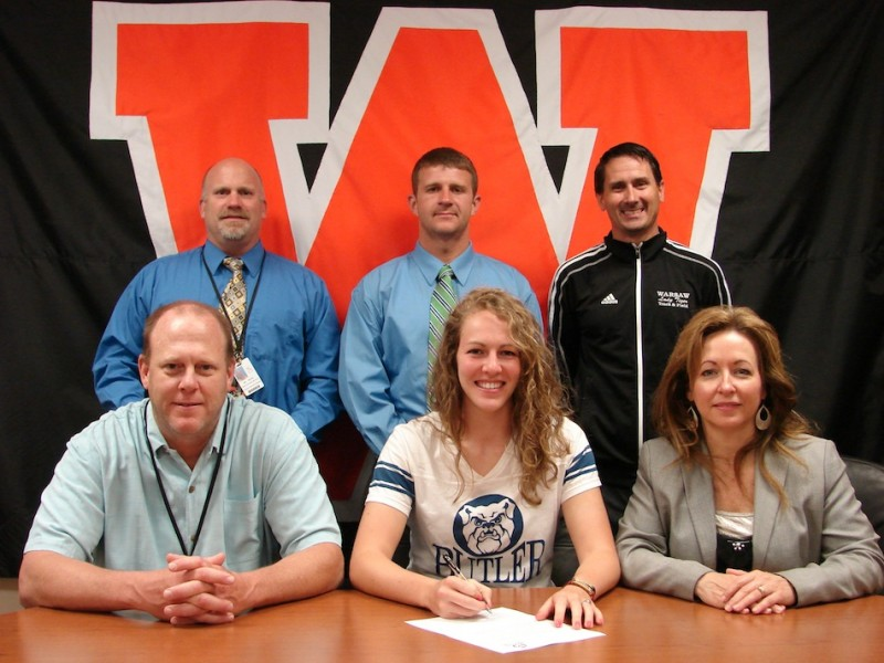 Warsaw senior Samantha Jensen will continue her track career at Butler University. The standout discus thrower is shown above in the front row flanked by her parents Phil and Debbie. In back are Warsaw Athletic Director Dave Anson, Warsaw throws coach David Bailey and Warsaw girls track coach Scott Erba (Photo provided)