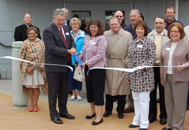 Warsaw Mayor Joe Thallemer cuts a ribbon symbolizing the opening of a new location for city offices at 102 S. Buffalo St., Warsaw, Saturday morning. On the left, Indiana State Rep. Rebecca Kubaki attended the event. To the right of the mayor is Warsaw City Council President Diane Quance, accompanied by several other city employees and contractors involved in the renovation of the building. (Photo by Jodi Magallanes)