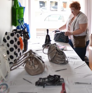 Joni Truex of Warsaw looks over a purse during a Saturday evening to raise money for Combined Community Services. Truex was the winner of a freshwater pearl necklace that was donated for the event.