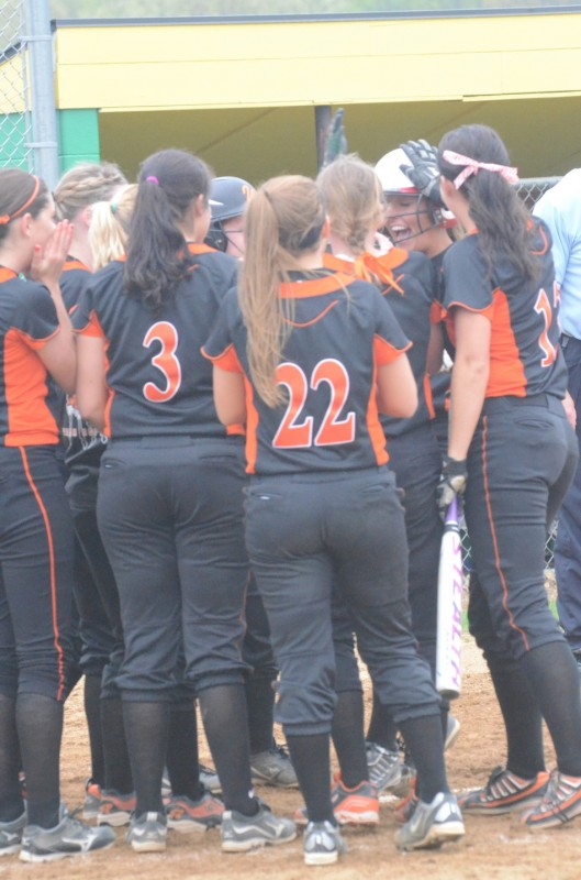 Members of the Warsaw softball team congratulate Ashley Ousley after she belted a home run Friday night.