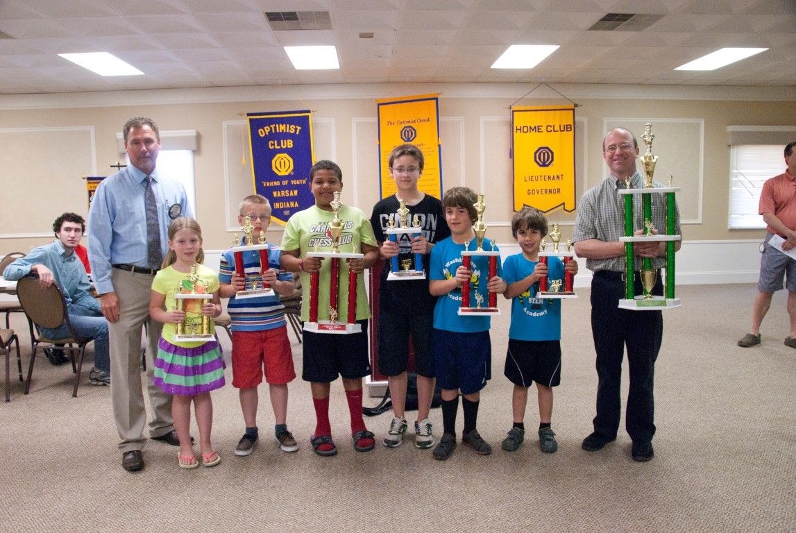 From left are Everett Nifong, Optimist Club; and students from the Madison School Chess Team displaying trophies they have won. They are Claire Reichenbach, Jonah Reichenbach, Isaiah Courtois, Jacob Lucas, Theodore Katris, Nicolas Katris and Jay Bolduc, chess coach.