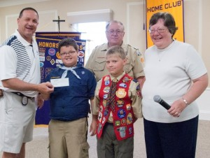 Tracy Furnival, left, president of Warsaw Breakfast Optimist Club, accepts a donation from Scout Wyatt Klinger, Scout Carson Kerlin and Scout Leader Sheri Reeve. In the back is Jim Reeve, Warsaw Breakfast Optimist and Scout Leader. (Photo provided)