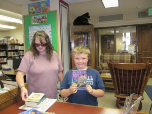 Evan and his mother, Trina Fidler, are shown selecting a good book. Evan said this is the first time ever that his name has been drawn for a prize. (photo provided)