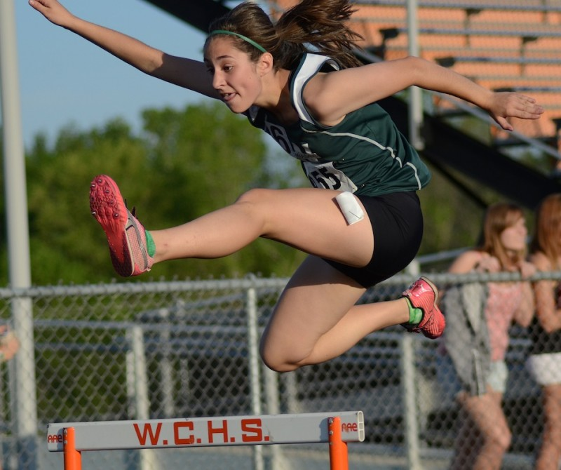 Wawasee freshman Sarah Lancaster soars over a hurdle during sectional action in Warsaw Tuesday night (Photos by Jim Harris)