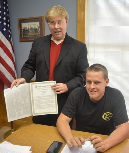 """Kosciusko County Republican Chairman Randy Girod presents Tom Beer, son of Robert """"Bob"""" Beer with a copy of the 113 Cngressional Record in which Robert Beer was honored"""