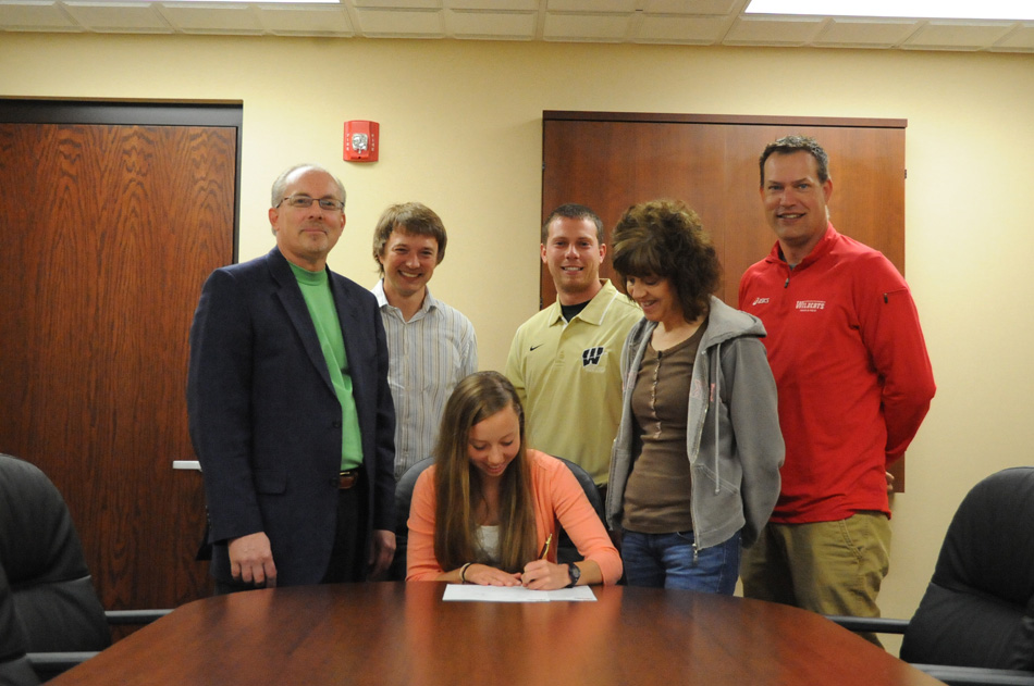 Wawasee High School senior Jen Slabaugh signs the dotted line in committing to Indiana Wesleyan University to continue her track and cross country careers. Slabaugh is joined by parents Brian and Kathy Slabaugh as well as Wawasee cross country and track coach Jerid Stoffel, Wawasee cross country and track coach Doug Slabaugh and Indiana Wesleyan University assistant coach Eric WHAT. (Photo by Mike Deak)