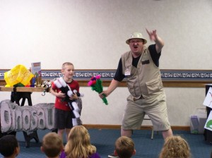 William Arford tries to wave different wands at the dinosaurologist to make the flowers appear.   (Photo provided)