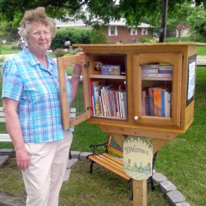 Ann MConnell stands next to the lending library she has made available at the end of her driveway on School Street, Leesburg