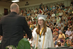 Emma Donahoe, Wawasee High School student, flashes a smile as she is presented her diploma by Don Harman, WHS principal during the graduation ceremonies Saturday morning. (Photo by Tim Ashley)